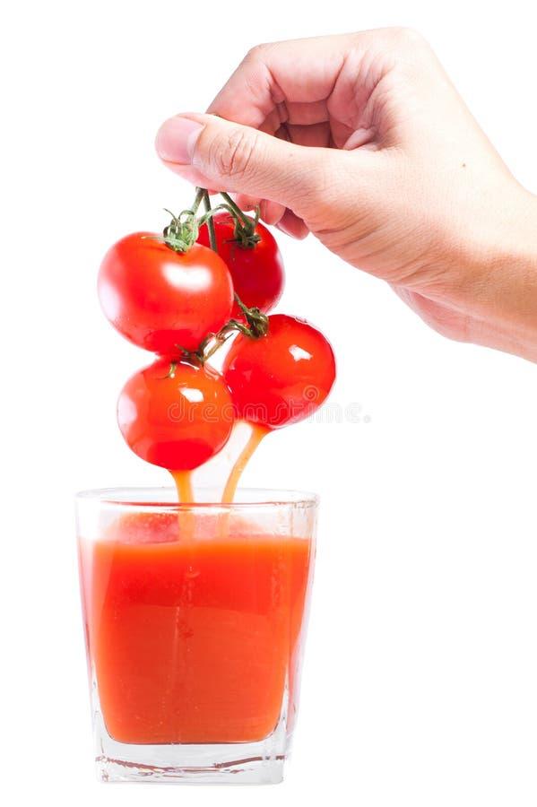 Suco fresco da baga do tomate que derrama no vidro foto de stock