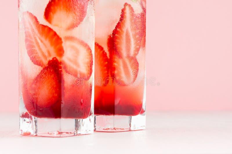 Suco frio da morango no vidro misted com bagas cortadas, cubos de gelo na tabela de madeira branca e rosa, close up, seção inferi imagens de stock