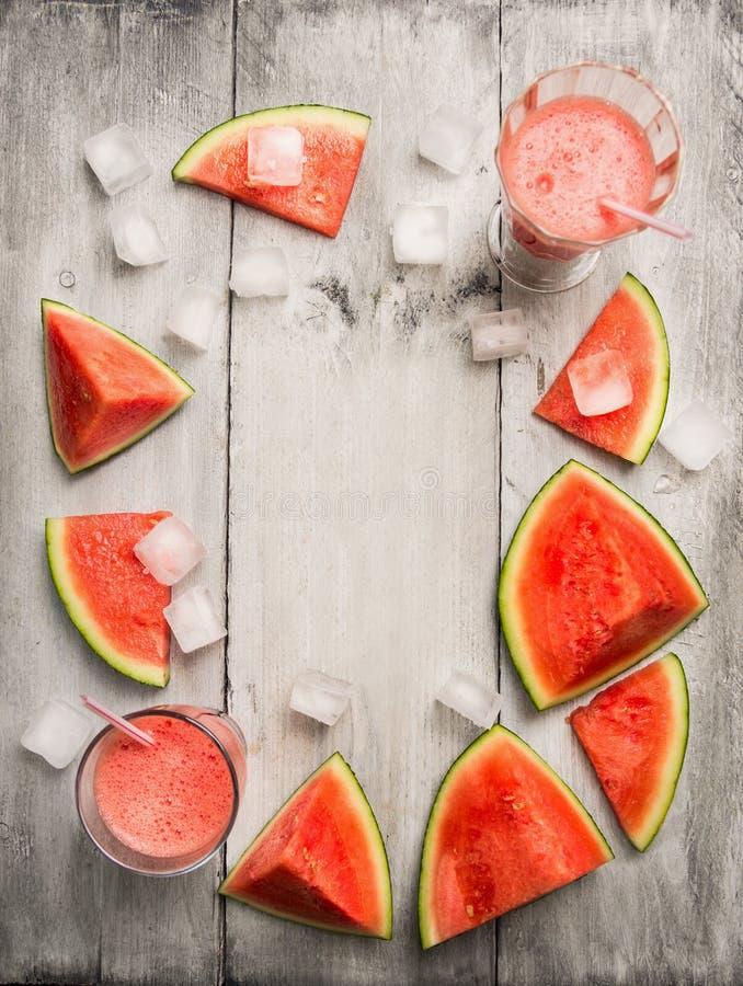 Suco ou batido da melancia com cubo de gelo e fruto cortado da melancia no fundo de madeira rústico, vista superior imagens de stock royalty free