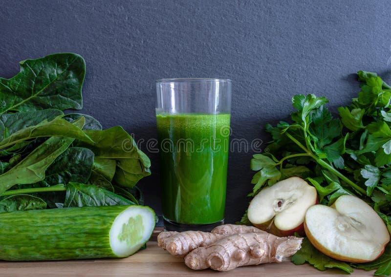 Suco saudável verde fresco da desintoxicação no vidro cercado por vegetais e por frutos fotografia de stock royalty free