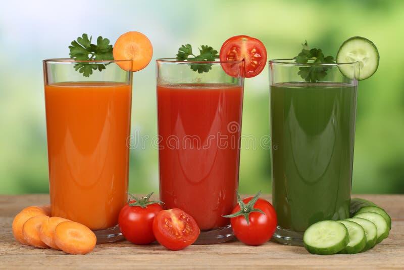 Suco vegetal das cenouras, dos tomates e do pepino imagens de stock royalty free
