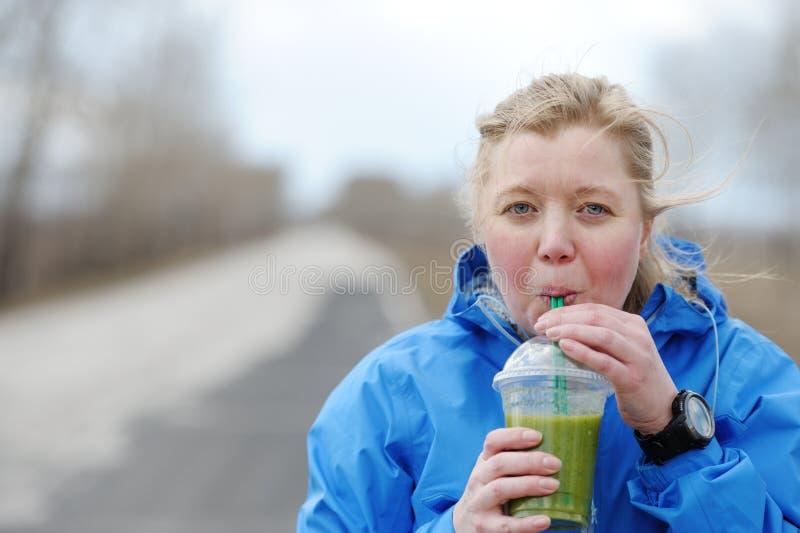 Suco vegetal verde do batido - batido bebendo da mulher como a parte fotos de stock