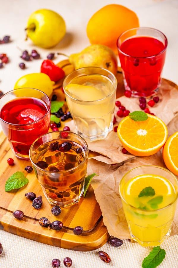 Sucos de fruta de baga e limonadas na placa de corte de madeira fotografia de stock royalty free