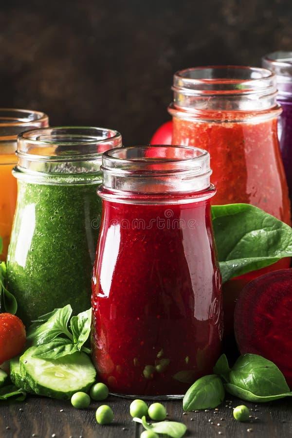 Sucos vegetais e batidos coloridos do tomate, cenoura, pimenta, couve, espinafre, beterrabas em umas garrafas na mesa de cozinha, imagens de stock royalty free