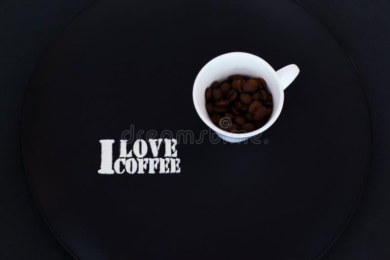 Sucre d'inscription et tasse blanche exclusive de porcelaine avec des graines de café de plat en céramique noir sur le fond noir  photographie stock libre de droits