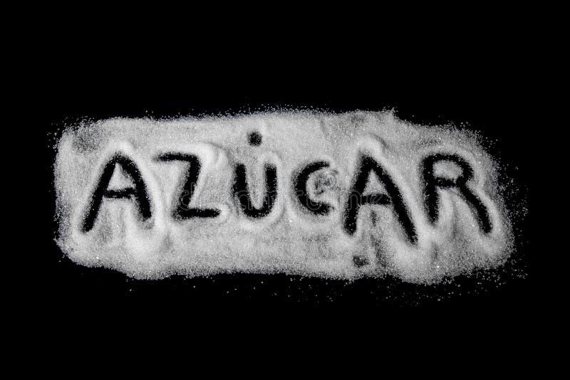 Sucre de Word écrit dans l'Espagnol du sucre granulé blanc et du sucre en poudre sur le fond en pierre foncé photo stock