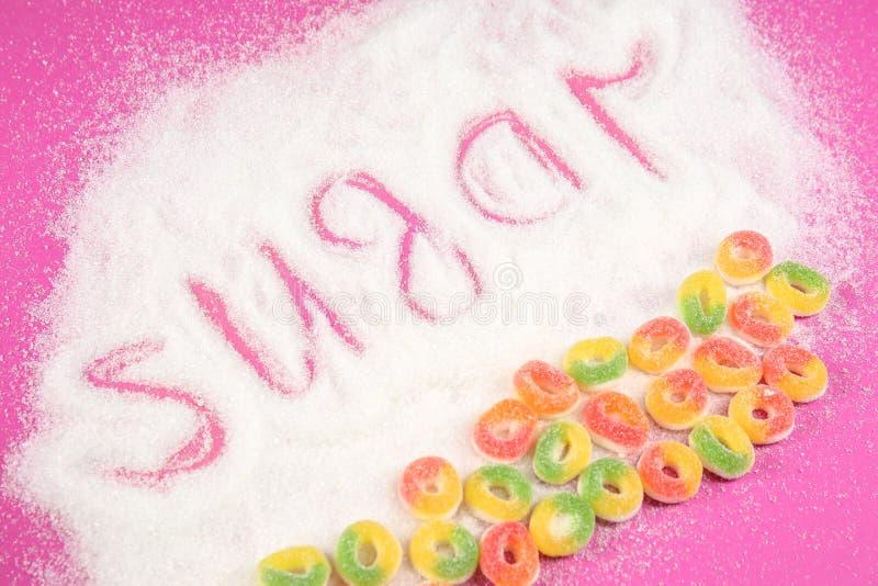 SUCRE de Word avec des bonbons sur le fond de couleur photos stock