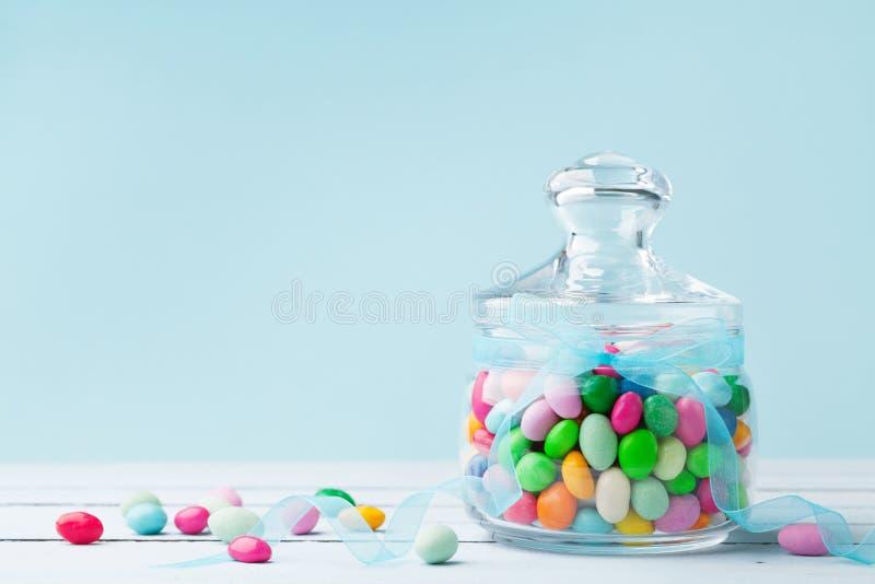 Sucrerie colorée dans le pot décoré du ruban d'arc sur le fond bleu Cadeaux pour l'anniversaire ou les Joyeuses Pâques image stock