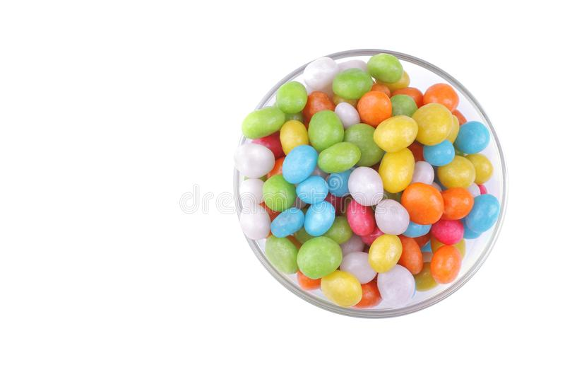 Sucrerie ronde multicolore dans un bol en verre sur un fond blanc D'isolement photo libre de droits