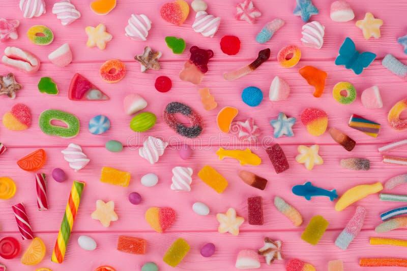 Sucreries colorées assorties sur un fond en bois rose image libre de droits
