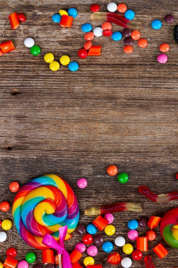 Sucreries colorées de Halloween sur le bois image stock