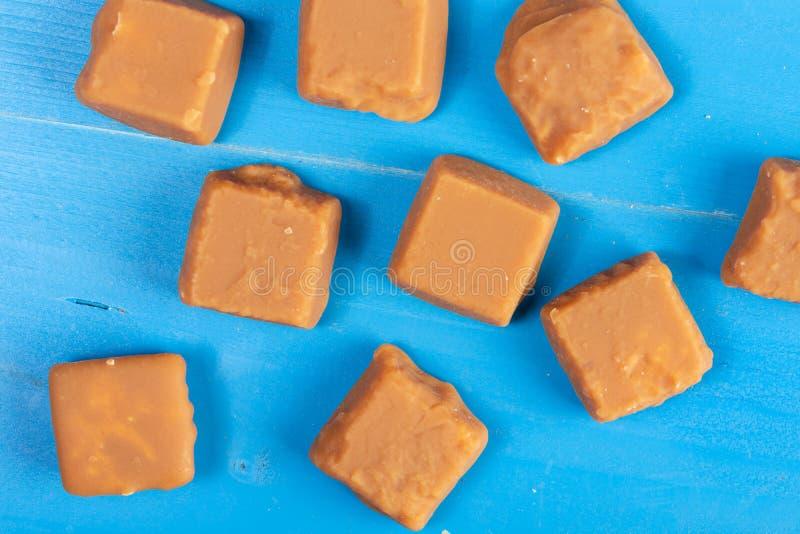 Sucreries de caramel de Brown sur les conseils en bois bleus images libres de droits