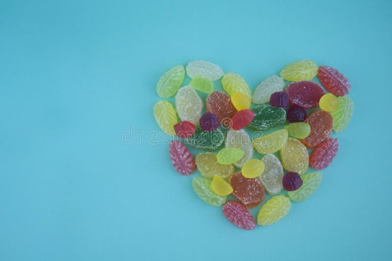 Sucreries de gélatine en sucre sur un fond bleu Coeur des bonbons images libres de droits