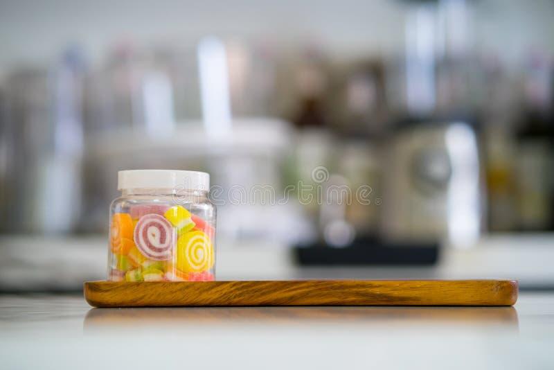 Sucreries douces colorées de gelée dans la bouteille du plat en bois au café photo libre de droits