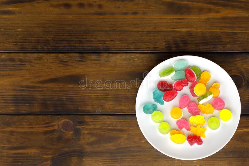 Sucreries en caoutchouc colorées dans une cuvette blanche sur une table en bois images libres de droits