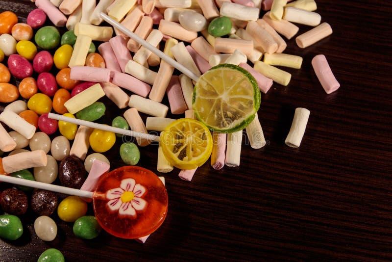 Sucreries, lucettes et guimauves colorées sur la table en bois photographie stock