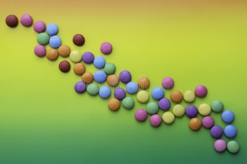 Sucreries multicolores avec le fond coloré image libre de droits