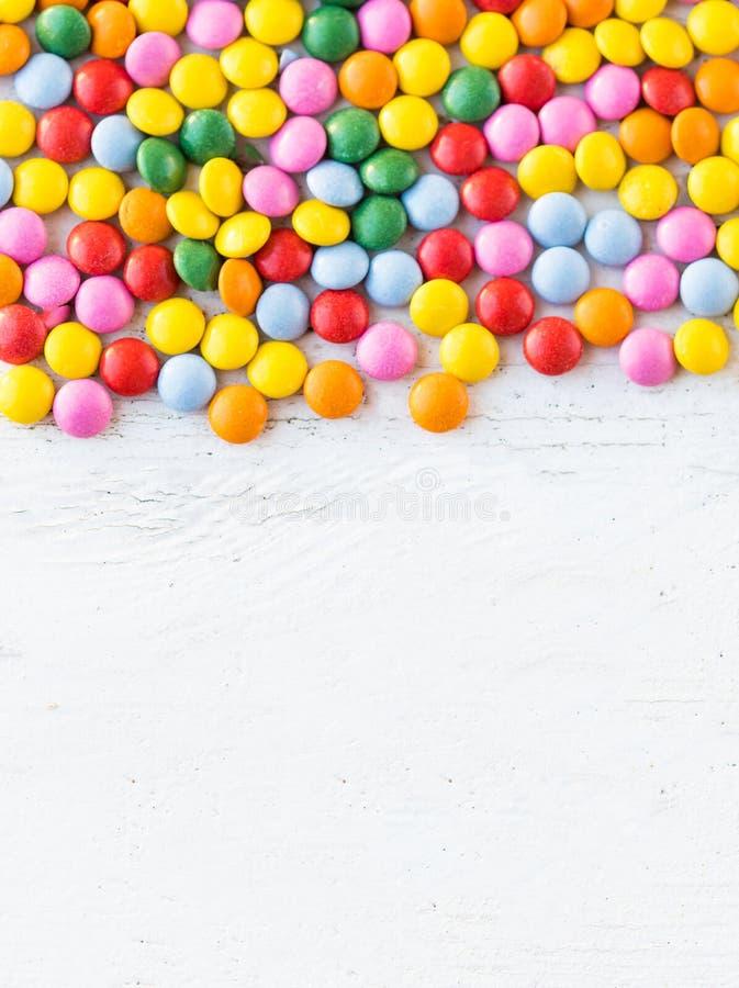 Sucreries rondes colorées sur le fond en bois rustique blanc avec c images libres de droits