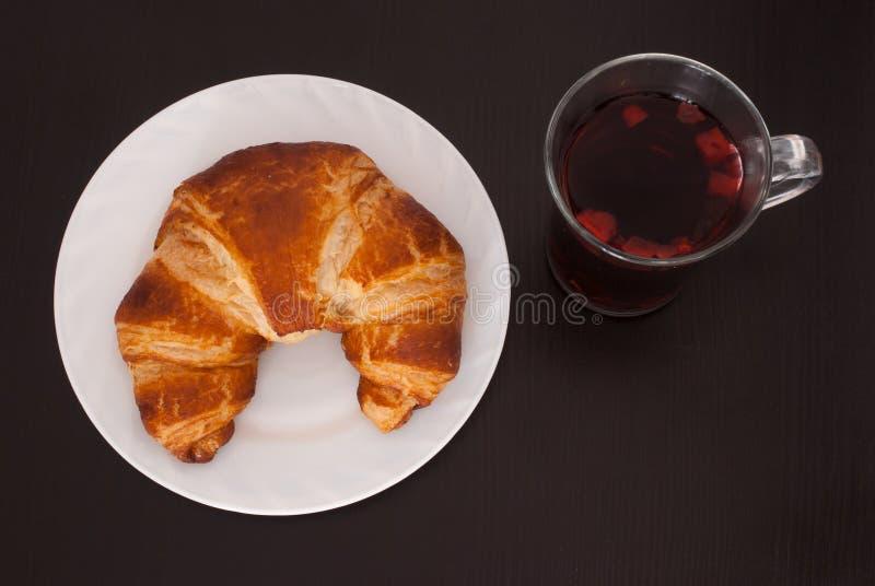 Sucrez le beignet enduit et un verre de thé de fruit sur le fond en bois noir images stock