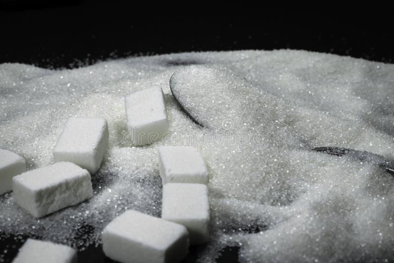 Sucrez les cubes et le sucre de grain dans une cuillère, pile sur le fond noir image libre de droits