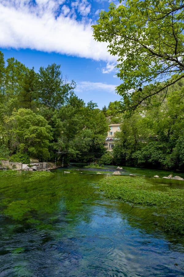 A sud della Francia, vista sulla piccola citt? di Provencal del poeta Petrarch Fontaine-de-Valchiusa con acque di verde smeraldo  immagini stock