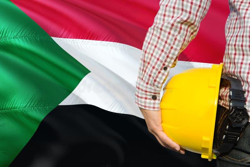 Sudański inżynier trzyma żółtego zbawczego hełm z machać Sudan chorągwianego tło Budowy i budynku poj?cie fotografia royalty free