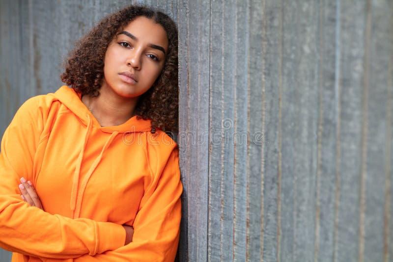 Sudadera con capucha anaranjada de la raza mixta de la mujer afroamericana triste del adolescente fotografía de archivo libre de regalías
