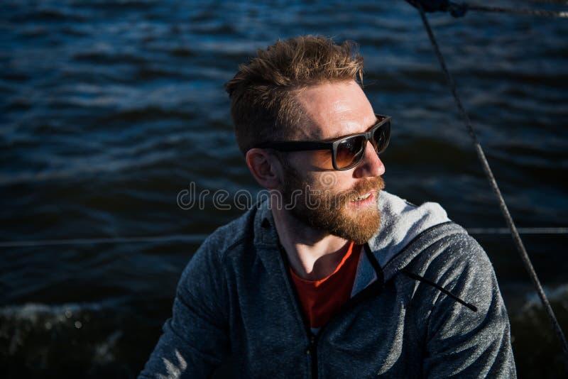 Sudadera con capucha el modelo barbudo ascendente cercano del hombre del retrato que lleva las gafas de sol y mira lejos, puesta  foto de archivo