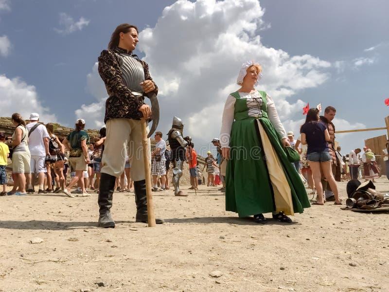 Sudak, Rusland - Augustus 16, 2015: rijke middeleeuwse ridder in de holdingsbijl van het staalpantser en een jong damemeisje in e stock afbeelding