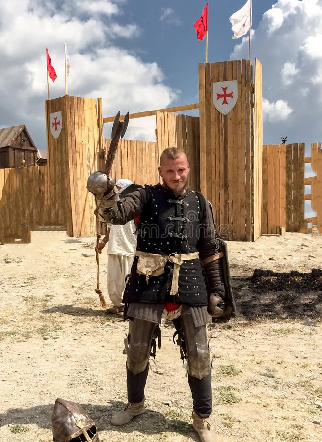 Sudak, Russia - August 16, 2015: handsome brutal man in the image of a knight in armor, armor, leather chainmail raised a battle stock images