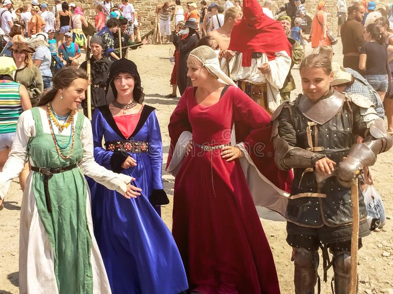 Sudak, Russia - August 16, 2015: three girls in dresses of medieval ladies and man in the armor of a medieval knight are chatting royalty free stock photo