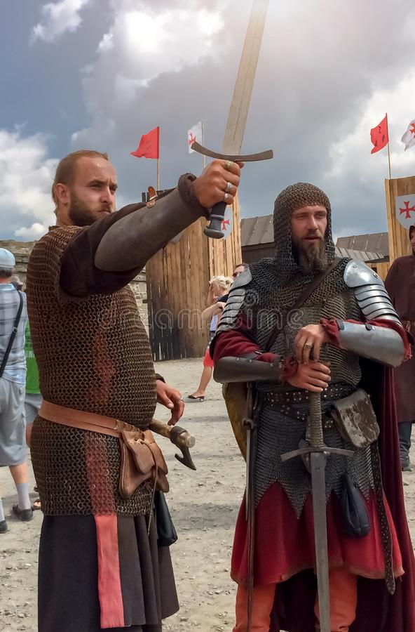 Sudak, Russia - August 16, 2015: two brutal men with beards in the costumes of medieval knights in chain mail, armor, one raised stock image