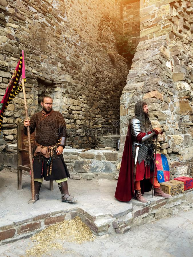Sudak, Russia - August 16, 2015: two powerful bearded mans in suit and image of a middle-aged knight in a helmet, chain, armor, stock photo