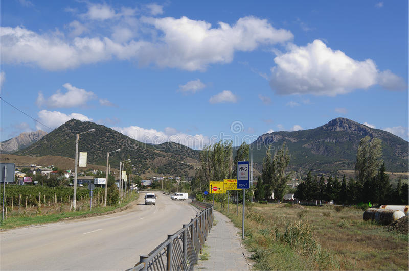 Sudak, Russia - September 24, 2014: mountainous surroundings of township, road with transport and guide signs stock image