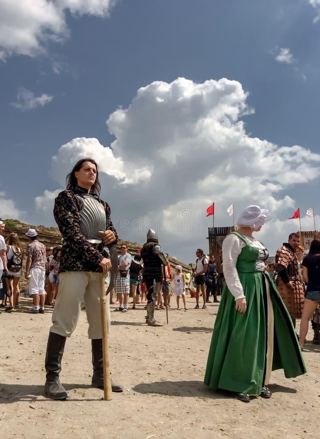Sudak, Russland - 16. August 2015: reicher mittelalterlicher Ritter in der Stahlrüstungsholdingaxt und in einem Mädchen junger Da stockfotos