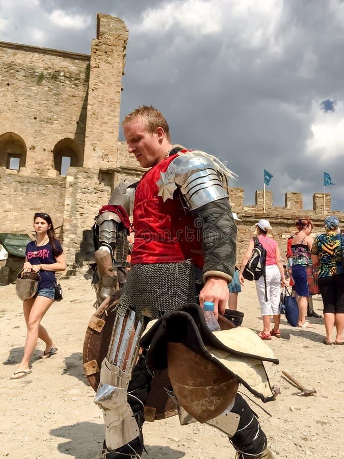 Sudak, Russland - 16. August 2015: starker Mann in der Rüstung des mittelalterlichen Ritters in der roten Kleidung, Kettenhemd, R lizenzfreie stockfotos