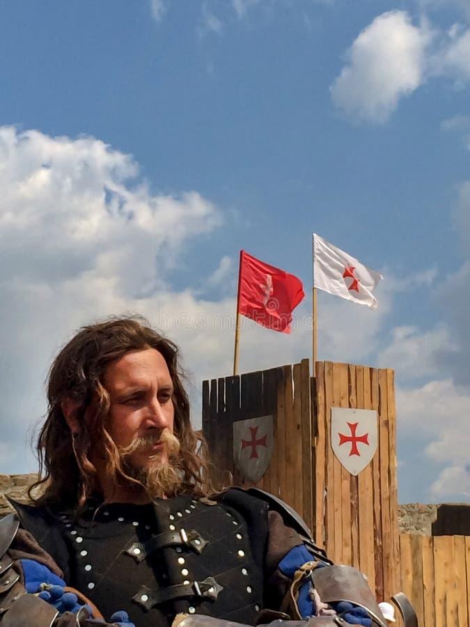 Sudak Ryssland - Augusti 16, 2015: brutal man med skägget, långt hår och en barsk blick i harnesken av en medeltida riddare mot a arkivbild