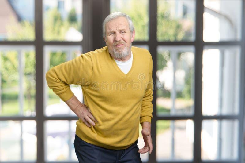 Sudden bottom back pain. Senior old grandpa in white woolen sweater having back pain. Checkered windows background stock photography