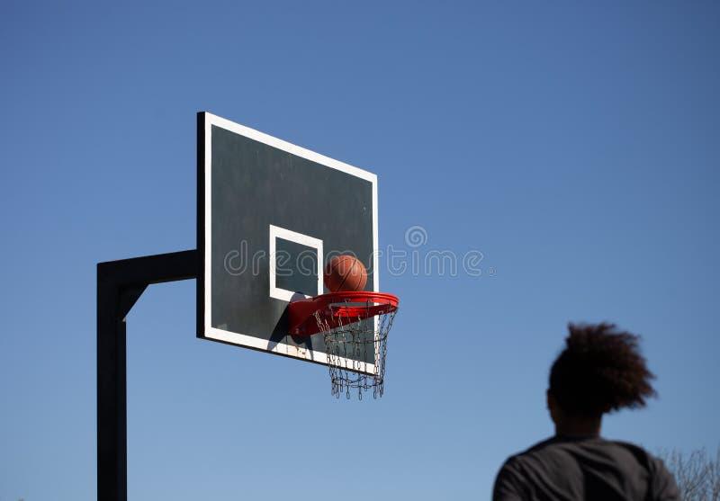 Suddig afrikansk amerikantonåring som skjuter en basket royaltyfri bild