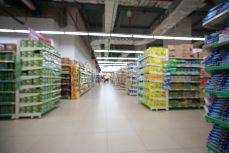 Suddig bakgrund för supermarket med färgrika hyllor och oigenkännliga kunder arkivbild