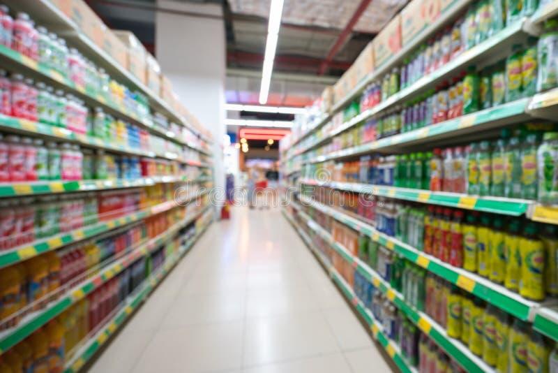 Suddig bakgrund för supermarket med färgrika hyllor och oigenkännliga kunder royaltyfri foto