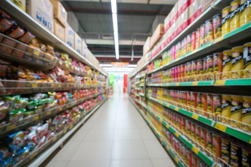 Suddig bakgrund för supermarket med färgrika hyllor och oigenkännliga kunder fotografering för bildbyråer