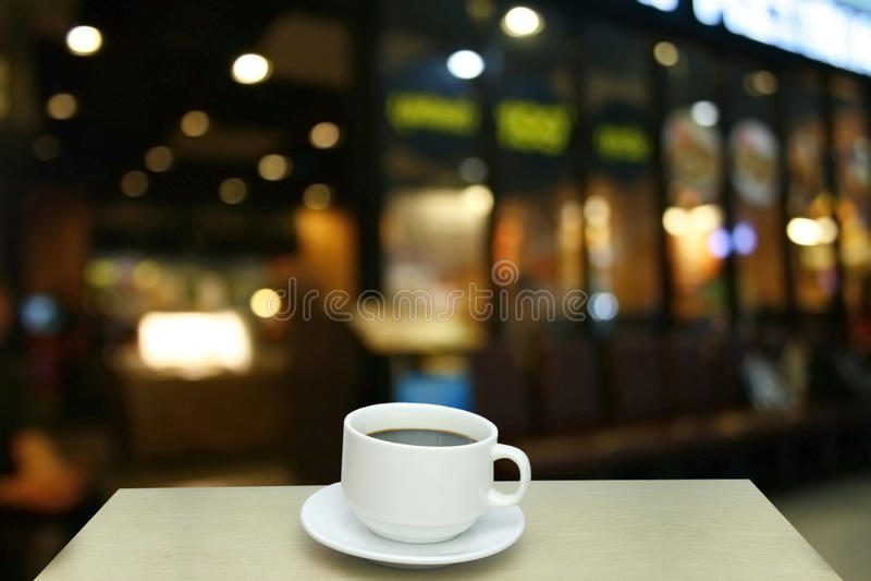 Suddig bakgrund: vit kopp kaffe och kund på restaur royaltyfria bilder