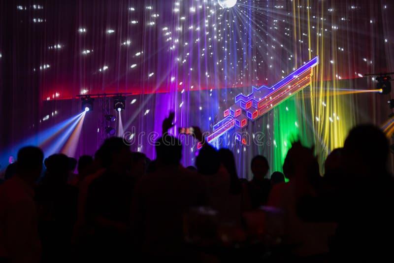 Suddig begreppsnattplats i konsertparti med åhörare och färgglad ledd belysning royaltyfri fotografi