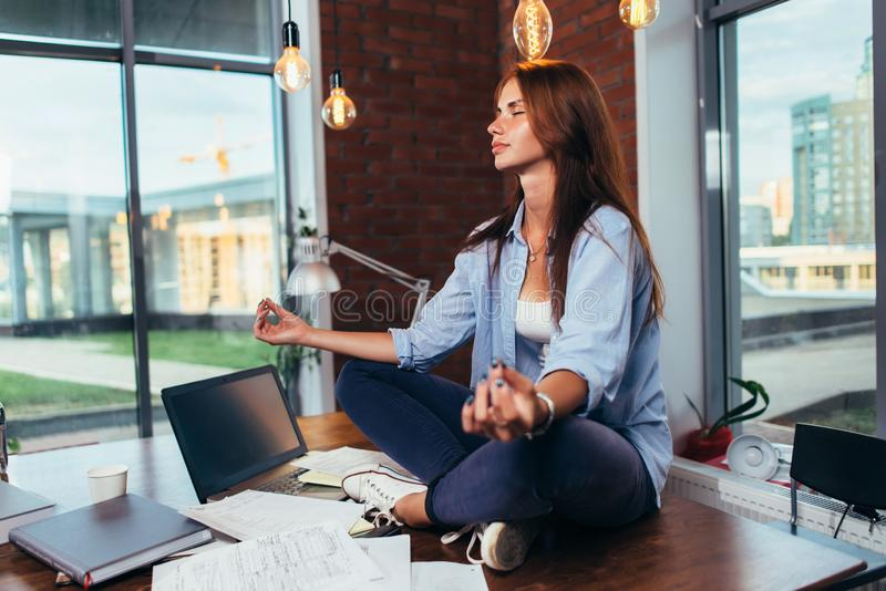 Suddig bild av den kvinnliga studenten som mediterar på skrivbordet i klassrumet som lugnar mening med hennes hand i fokus royaltyfri bild