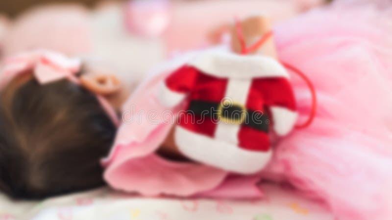 Suddig bild av Littte den förtjusande nyfödda asiatiska flickan, 1 till 2 månader, med den hållande miniatyrröda Santa Claus för  arkivbild