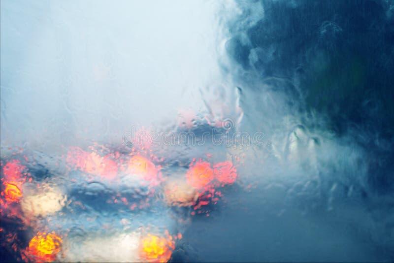 Suddig bild av trafik till och med en bilvindruta under hällregn royaltyfri fotografi