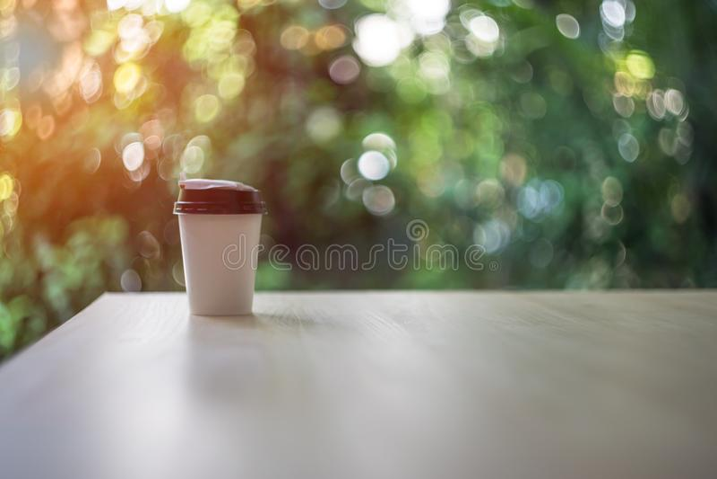 Suddig disponibel kaffekopp på trätabellen över trädgårds- landskap med solljus royaltyfria foton