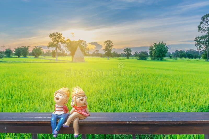 Suddig för abstrakt kontur mjuk och mjuk fokus av solnedgången med pojke- och flickatecknad filmdockan på träplatsen, ric grön ri royaltyfria bilder