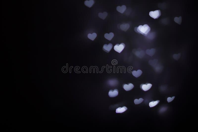 Suddig för formbokeh för purpurfärgad hjärta bakgrund arkivfoton